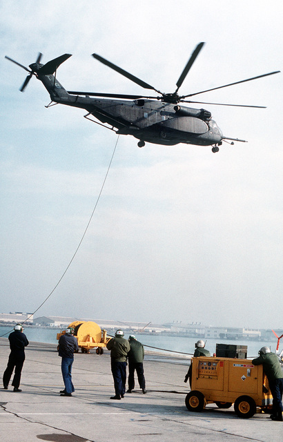 Ground crewmen stand by as an MH-53E Sea Dragon helicopter from Helicopter Mine Countermeasures Squadron 15 (HM-15) passes overhead trailing a tow cable for a Mark 105 minesweeping exercise
