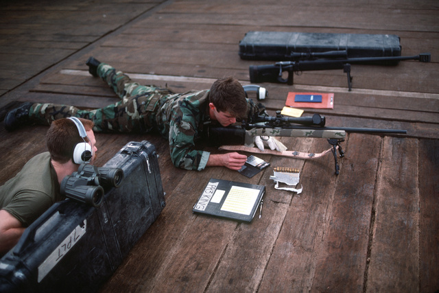 Location: Persian Gulf. A member of a special warfare unit uses a calculator to compete changes in windage and elevation before firing another round from his M600 7.62 mm sniping rifle on the deck of the barge HERCULES. Various Navy units are operating in the gulf in support of efforts to provide security for US flagged shipping in the area