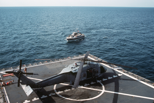 Location: Persian Gulf. Two crewmen get some exercise on flight deck beside an SH-60 Sea Hawk helicopter as a PB Mark III patrol boat approaches the barge HERCULES during operations supporting Navy efforts to provide security for US-flagged shipping in the gulf