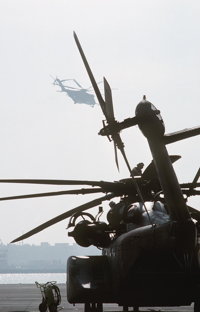 Maintenance crewmen work atop an MH-53E Sea Dragon helicopter from Helicopter Mine Countermeasures Squadron 15 (HM-15) as another Sea Dragon passes overhead