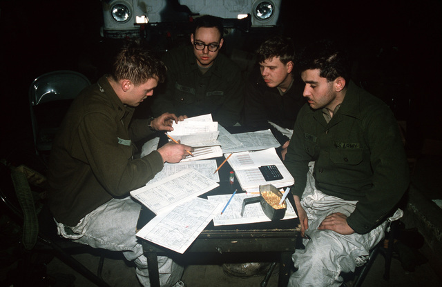 Members of the 706th Maintenance Battalion go over maintenance reports during Exercise BRIM FROST '89