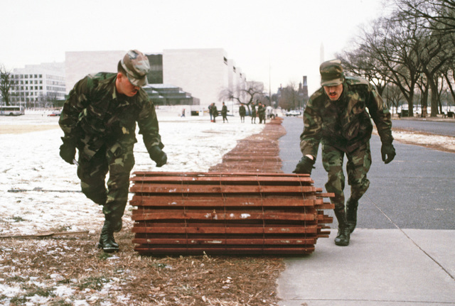 Private First Class (PFC) Michael Johnson, Company B, 11th Engineer Battalion, and PFC George Hammond, 30th Engineer Battalion, unroll a snow fence on the mall in preparation for the inaugural ceremonies for President-elect George H.W. Bush