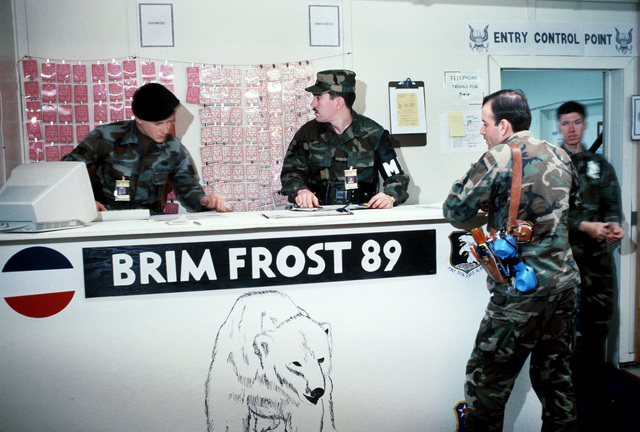 SGT Bart Wortz of the 380th Security Police Squadron consults a list as PFC Claude Durham, 56th Military Police Company, looks over identification tags at the front desk of the Joint Exercise Control Group headquarters. The group is a unit of Forces Command which will control the various phases of the joint service exercise Brim Frost '89