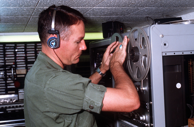 SSG Peter Burt, station manager for Southern Command Network (SCN), puts a radio program in a reel-to-reel tape player