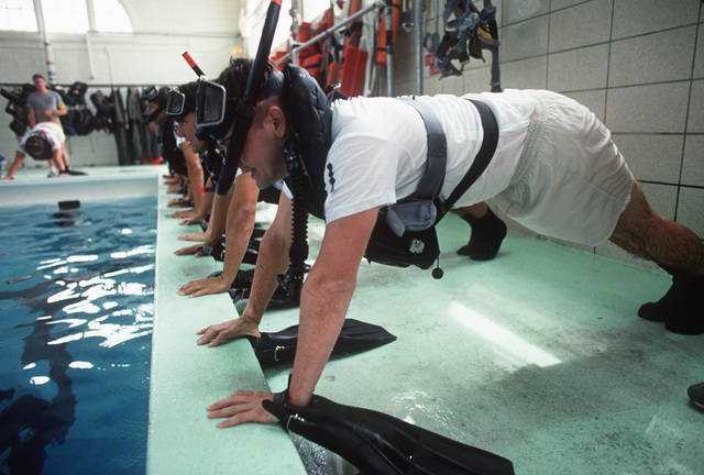 Students at the Navy Rescue Swimmers School assume the push-up position during a class at the pool. After completing the four-week course, the students will become certified search and rescue swimmers