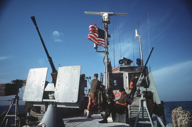 Surrounded by the various heavy machine guns and cannon with which their vessel is armed, three crewmen aboard a PB Mark III patrol boat stand easy as another patrol nears an end. The patrol boat is among the Navy assets operating in support of efforts to provide security for US-flagged shipping in the gulf