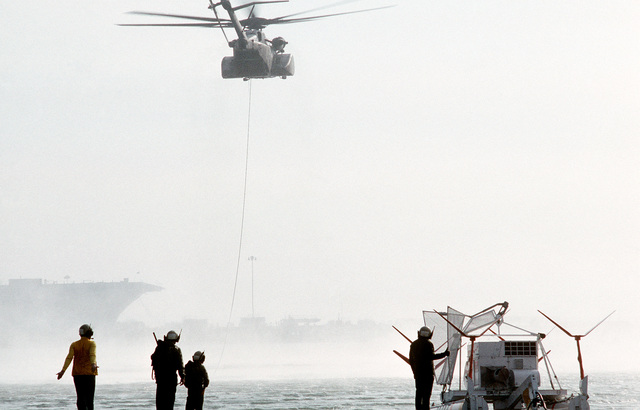 Trailing a tow line attached to the Mark 105 minesweeping sled at right, an MH-53E Sea Dragon helicopter from Helicopter Mine Countermeasures Squadron 15 (HM-15) heads out over San Francisco Bay for a minesweeping exercise