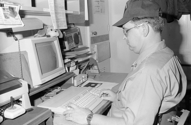A chief petty officer works at a computer workstation aboard the amphibious assault ship USS BELLEAU WOOD (LHA 3)