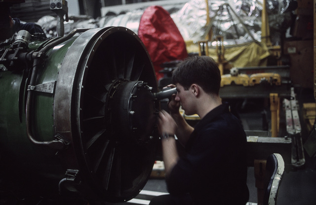 An aviation maintenance technician works on a jet engine in the hangar bay of the aircraft carrier USS RANGER (CV 61).  The RANGER is operating off the coast of Southern California