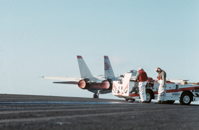 An F-14A Tomcat aircraft is launched from the aircraft carrier USS RANGER (CV 61) as a crash vehicle and firefighters stand by.  The RANGER is participating in flight operations off the coast of Southern California