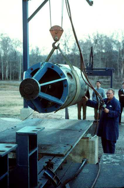 A plant employee steadies a propulsion stage from a Pershing 1A missile as it is lowered into place on a firing stand. Several missiles are being destroyed in the presence of Soviet inspectors in accordance with the Intermediate-Range Nuclear Forces (INF) Treaty