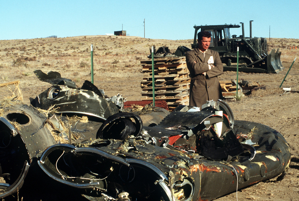 A Soviet inspector stands beside the mangled remnants of two Pershing II missile stages. Several missiles are being destroyed in the presence of Soviet inspectors in accordance with the Intermediate-Range Nuclear Forces (INF) Treaty