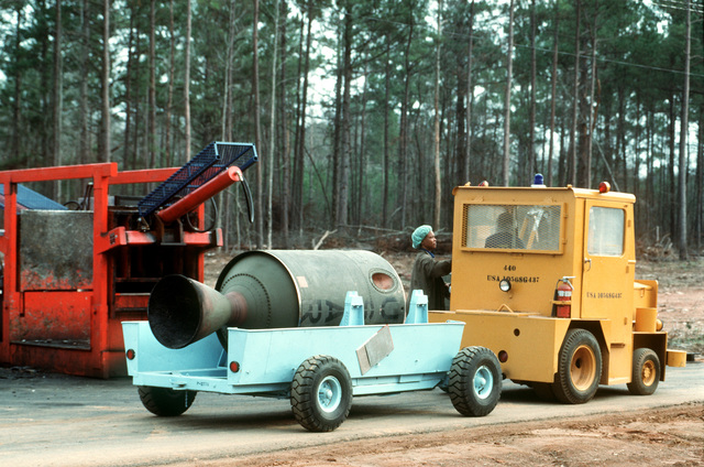 A spent propulsion stage of a Pershing 1A missile is transported in a trailer to a crusher, where its destruction will be completed. Several missiles are being destroyed in the presence of Soviet inspectors in accordance with the Intermediate-Range Nuclear Forces (INF) Treaty