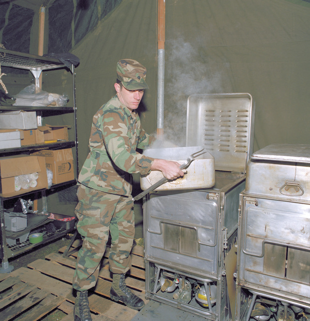A mess management specialist lifts a steaming pot from a stove in a field kitchen set up by the 513th Military Intelligence Group