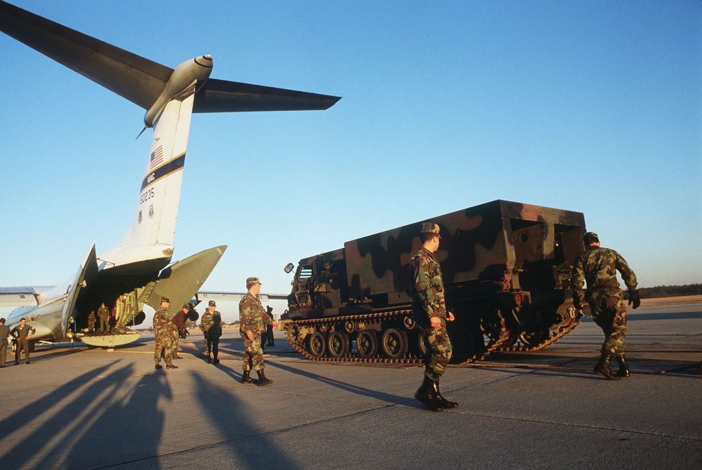 Airmen stand by as an M-270 multiple launch rocket system (MLRS) as the vehicle moves toward a C-141B Starlifter aircraft. The loading of the MLRS onto the plane will represent the first time that such artillery equipment has been placed aboard a Starlifter. The MLRS is assigned to Battery B, 3rd Battalion, 27th Field Artillery, XVIII Airborne Corps