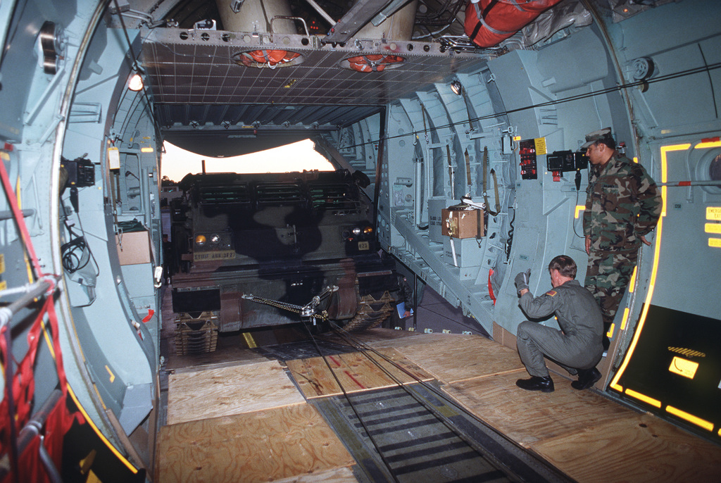 Sergeant Stephen J. Tkach III, a loadmaster with the 4th Military Airlift Squadron, directs the winching of an M-270 multiple launch rocket system (MLRS) onto a C-141B Starlifter aircraft. The loading of the MLRS onto the plane represents the first time that such artillery equipment has been placed aboard a Starlifter. The MLRS is assigned to Battery B, 3rd Battalion, 27th Field Artillery, XVIII Airborne Corps