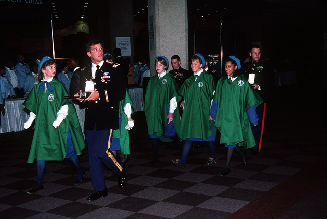 Military personnel escort participants to the stage for the Presidential Pageant being held in honor of George H.W. Bush, 41st president of the United States
