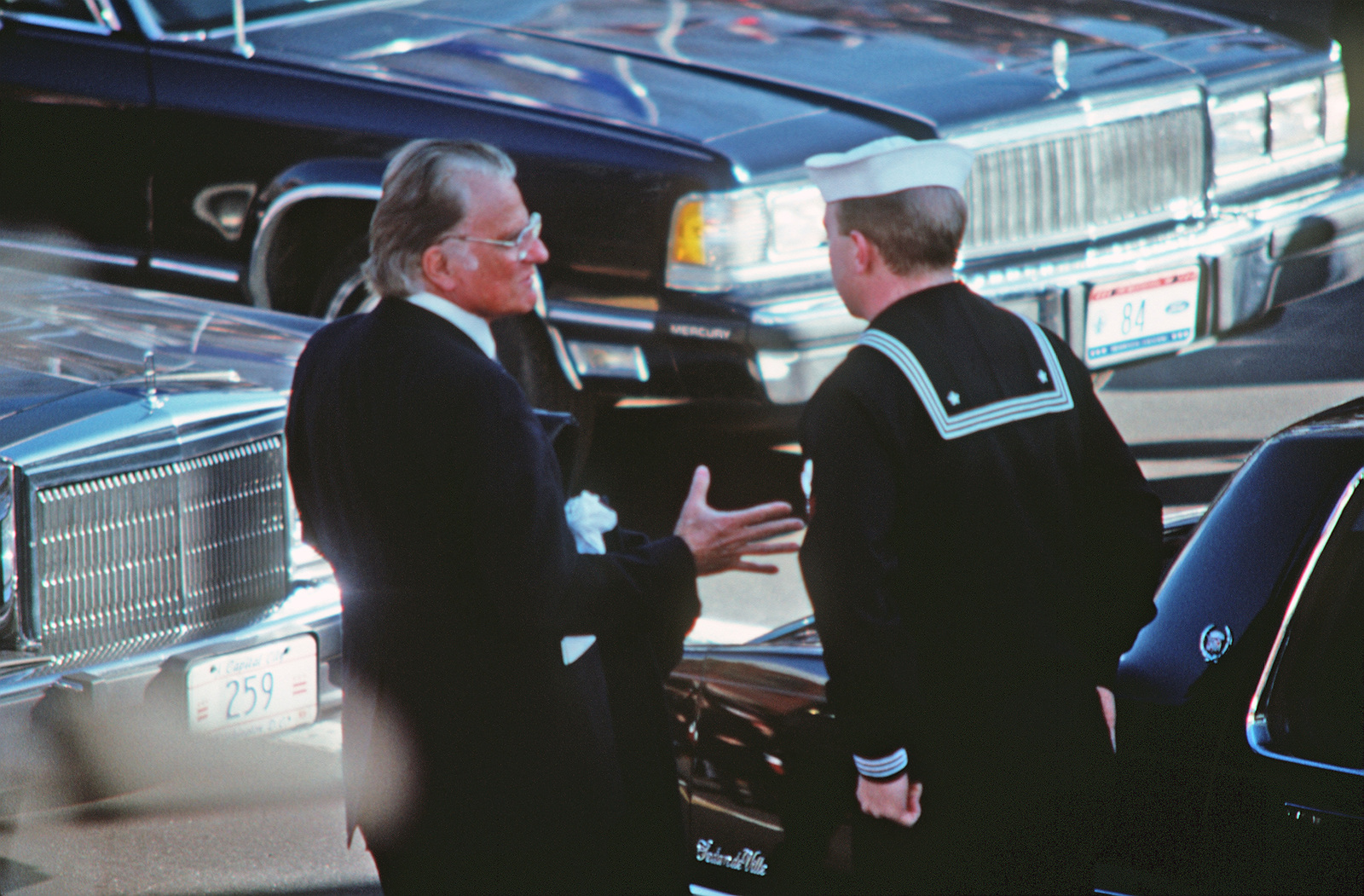 A Sailor assists Reverend Billy Graham from his car and directs him to the reviewing stand on Pennsylvania Avenue prior to the Inauguration Day parade for George H.W. Bush, 41st president of the United States