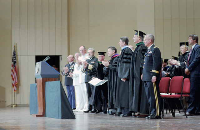 President Ronald Reagan with Caspar Weinberger and C. Everett Koop during Remarks at the Uniformed Services University of Health Sciences Commencement Ceremony at the Kennedy Center in Washington, DC