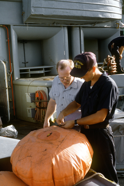 Crewmen prepare marker buoys on the deck of the salvage ship USS GRASP (ARS-51). The GRASP is participating in a salvage operation to free the grounded destroyer USS SPRUANCE (DD-963). The SPRUANCE ran aground off Andros Island, Bahamas, January 25, 1989