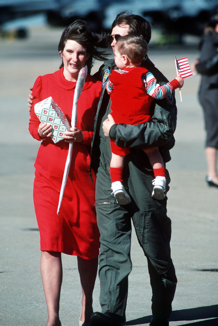His wife's tears of joy greet a returning aviator of Fighter Squadron 32 (VF-32) from the aircraft carrier USS JOHN F. KENNEDY (CV 67). In his other arm he holds his baby with a small American flag