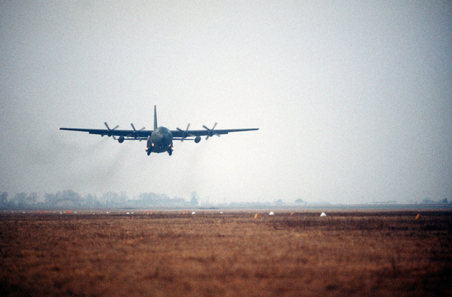 A 37th Tactical Airlift Squadron C-130E Hercules aircraft descends for a grass strip landing at Drop Zone Juliet near Aviano Air Base during an evening training mission