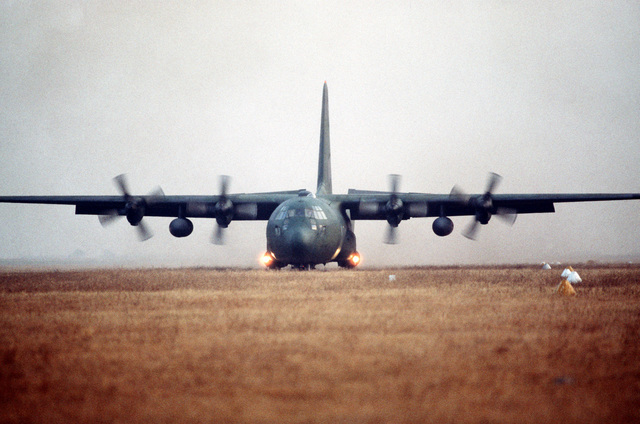 A 37th Tactical Airlift Squadron C-130E Hercules aircraft makes a grass strip landing at Drop Zone Juliet near Aviano Air Base during an evening training mission