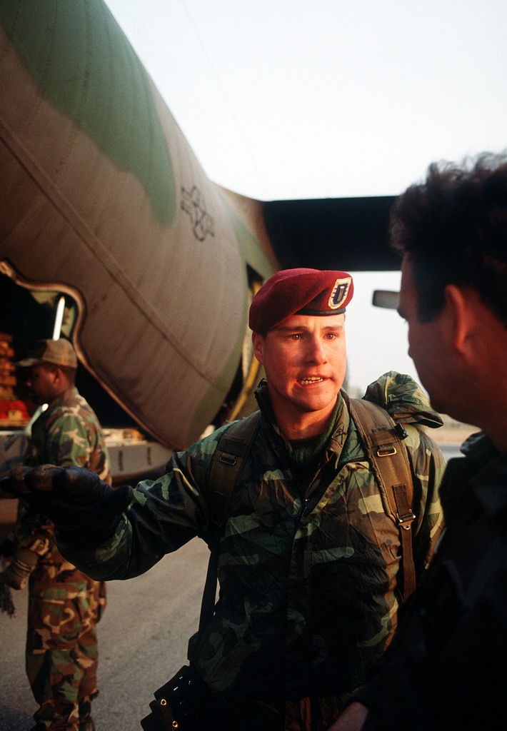 Air Force personnal confer during the loading of a C-130E Hercules aircraft for sequential heavy airdrop practice by the 37th Tactical Airlift Squadron