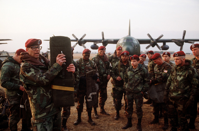 Airborne troops of the 3rd Battalion, 325th Infantry, ready their packs and parachutes for an evening training mission. They are jumping from C-130E Hercules aircraft of the 37th Tactical Airlift Squadron