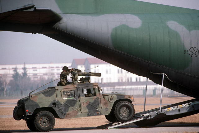 An M998 high mobility multipurpose wheeled vehicle carrying a tube-launched, optically tracked, wire guided (TOW) missile launcher is loaded into a C-130E Hercules aircraft for sequential heavy airdrop practice by the 37th Tactical Airlift Squadron