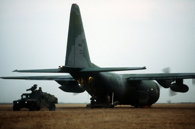 An M998 high mobility multipurpose wheeled vehicle carrying a tube-launched, optically tracked, wire guided (TOW) missile launcher is offloaded from a 37th Tactical Airlift Squadron C-130E Hercules aircraft that has made a grass strip landing at Drop Zone Juliet near Aviano Air Base during an evening training mission