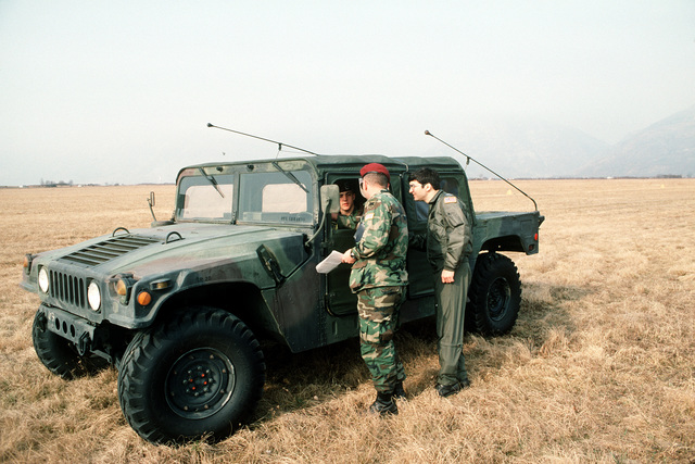 Captain D.E. Stewart of the 37th Tactical Airlift Squadron and two airmen, one in an M998 High mobility multipurpose wheeled vehicle, discuss their survey of Drop Zone Juliet, near Aviano Air Base
