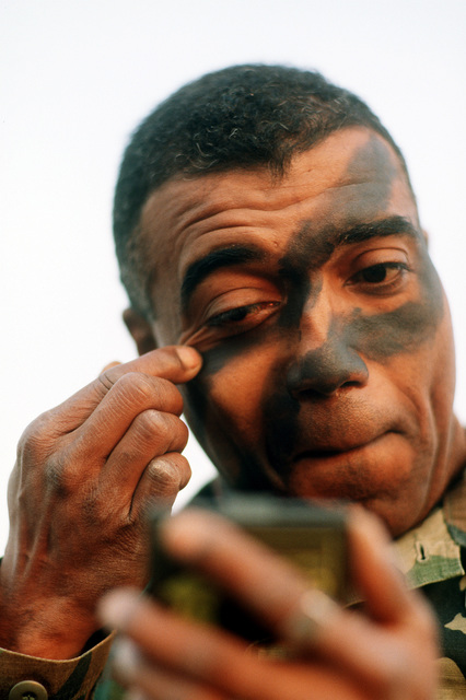 First Sergeant Lawrence Brooks, Headquarters and Headquarters Company, 3rd Battalion, 325th Infantry, puts on camouflage greasepaint for an evening airdrop training mission with the 37th Tactical Airlift Squadron