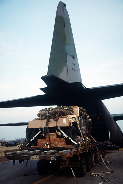 M998 high mobility multipurpose wheeled vehicles are loaded from a K-loader into a C-130E Hercules aircraft for sequential heavy airdrop practice by the 37th Tactical Airlift Squadron