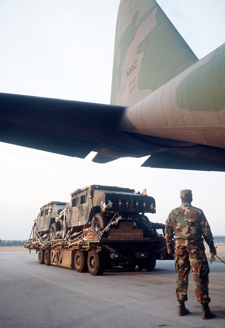 M998 high mobility multipurpose wheeled vehicles are loaded into a C-130E Hercules aircraft for sequential heavy airdrop practice by the 37th Tactical Airlift Squadron