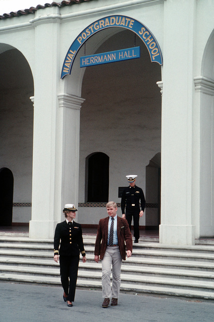 Three students walk down the front steps of Herrmann Hall on the campus of the Naval Postgraduate School