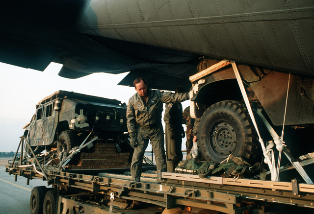 M998 High-Mobility Multipurpose Wheeled Vehicles (HMMWV) are loaded from a K-loader into a C-130E Hercules aircraft for sequential heavy airdrop practice by the 37th Tactical Airlift Squadron