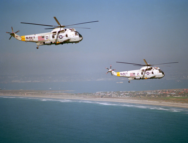 A right side view of two SH-3H Sea King helicopters from Helicopter Anti-submarine Squadron 2 (HS-2) flying along the coast as they return from a Western Pacific deployment