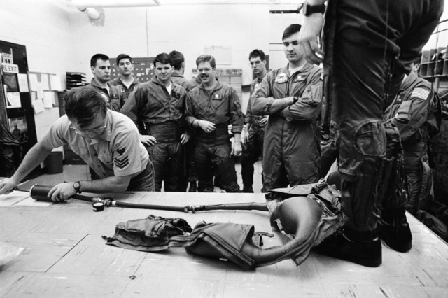 Aircrew Survival Equipmentman First Class Harry Drake shows student naval flight officers how to inflate a G-suit during a Training Squadron 10 (VT-10) class