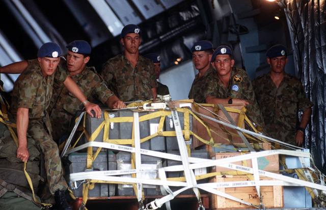 Australian troops prepare to push a pallet of supplies out of a US 60th Military Airlift Wing C-5A Galaxy aircraft during operation ELECTION DISTRICT. THE C-5 is transporting a contingent of Royal Australian Engineers to assist United Nations Transition Assistance Group (UNTAG) peacekeeping forces in preparation for the November 1989 elections and independence of Namibia