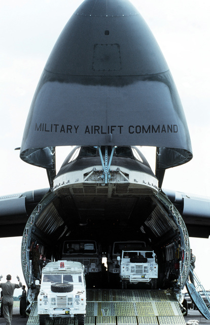 STAFF Sergeant Donald Dufresne Sr., 9th Military Airlift Squadron, directs the unloading of United Nations Transition Assistance Group (UNTAG) Land Rover vehicles from a 60th Military Airlift Wing C-5A Galaxy aircraft during operation ELECTION DISTRICT. The C-5 is transporting a contingent of Royal Australian Engineers to assist UNTAG peacekeeping forces in preparation for the November 1989 elections and independence of Namibia