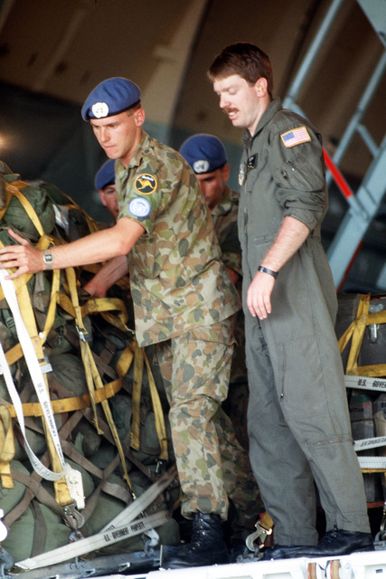 STAFF Sergeant James A. Noble of the 9th Military Airlift Squadron helps Australian troops to push a pallet of supplies out of a 60th Military Airlift Wing C-5A Galaxy aircraft during operation ELECTION DISTRICT. THE C-5 is transporting a contingent of Royal Australian Engineers to assist United Nations Transition Assistance Group (UNTAG) peacekeeping forces in preparation for the November 1989 elections and independence of Namibia