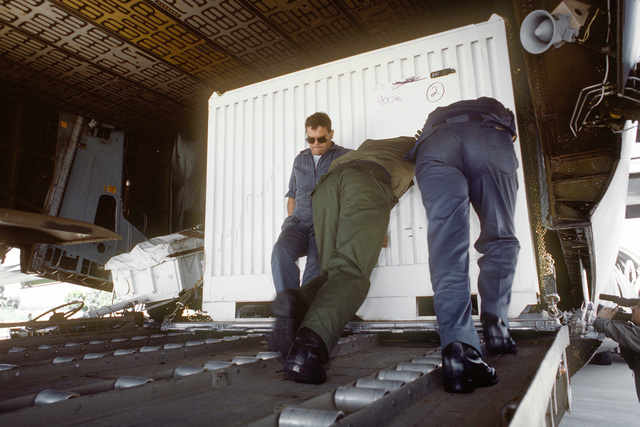 U.S. and Australian personnel push a container of equipment and building materials into a U.S. 60th Military Airlift Wing C-5A Galaxy aircraft during OPERATION ELECTION DISTRICT. It will be used for barracks and facilities construction by a contingent of Royal Australian Engineers who are assisting United Nations Transition Assistance Group (UNTAG) peacekeeping forces in preparation for the November 1989 elections and independence of Namibia