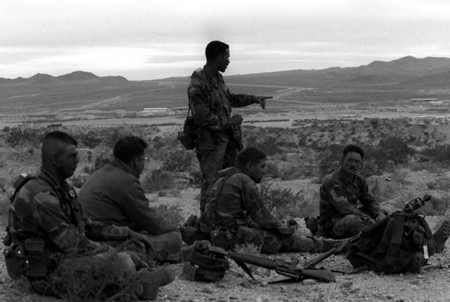Five soldiers takes a break after a day-long defensive exercise during their unit's deployment to the National Training Center