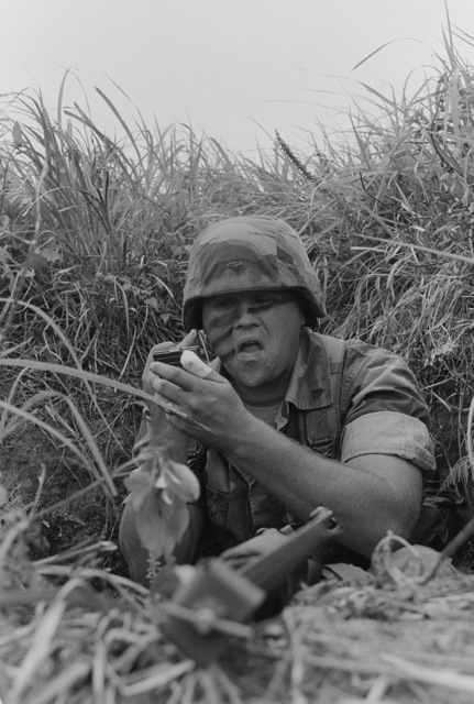 A Marine from the 9th Expeditionary Brigade applies camouflage during a field operation