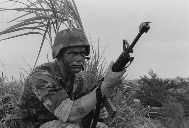 A Marine from the 9th Expeditionary Brigade armed with an M16A2 rifle maintains a defensive position during a field operation