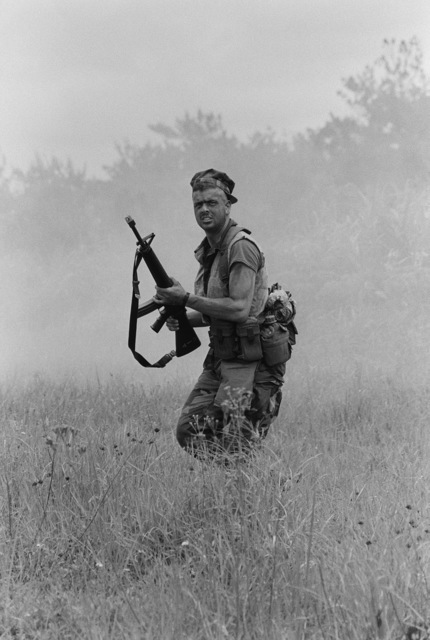 A Marine from the 9th Expeditionary Brigade armed with an M16A2 rifle moves across a field under the concealment of a smoke grenade during a field operation