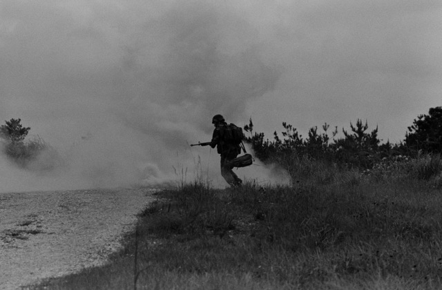 A Marine from the 9th Expeditionary Brigade runs across a field under the concealment of a smoke grenade during a field operation