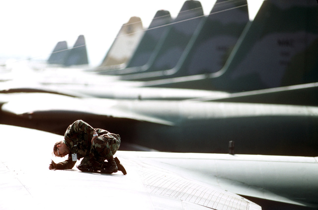 Sergeant Joe Birdwell, 435th Organizational Maintenance Squadron, checks the top of a wing on a C-130E Hercules aircraft, parked in a row of C-130s on the flight line during 37th Tactical Airlift Squadron participation in an Army training and evaluation program (ARTEP) mission
