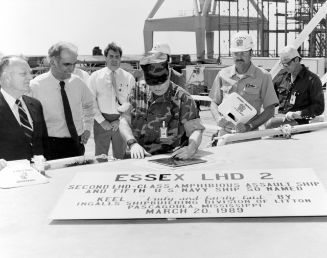 General Alfred M. Gray Jr., commandant of the Marine Corps, authenticates the keel plaque at the keel laying ceremony for the LHD-class amphibious assault ship USS ESSEX (LHD 2). Standing by during the signing are, from left: E.E. Shoults, program manager, Amphibious Warfare and Strategic Sea Lift Program; J St. Pe', president, Ingalls Shipbuilding, Inc., General Gray; Captain M.G. Simpson, suprervisor of Shipbuilding, Conversion and Repair, Pascagoula; and Joe Smith, welder